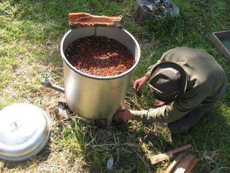 smiley underdog firing up the bark boiler full of shredded tan oak bark for tanning goat skins.