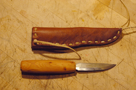 My friend brought over this knife to make a sheath. I've got an outline made for a video on knife handle design and had to entirely reshape the handle first, which turned into a video segment. The sheath is made from 4 different leathers, stiff bark tanned wild boar on the inside, soft goat on the outside, a horse hide welt to protect the stitching and braintanned buckskin sewing thong. It turned out pretty sweet. I'm not a big fan of this mora style of blade for general purpose knives, but that puts me in a minority among the primitive skills crowd.